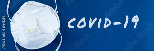 Fotografía Face mask on blue background with covid-19 written in white colour in conceptual image of public health threatening virus