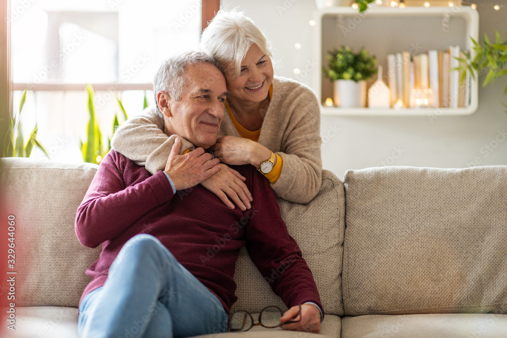 Fototapeta Portrait of a happy senior couple relaxing together at home