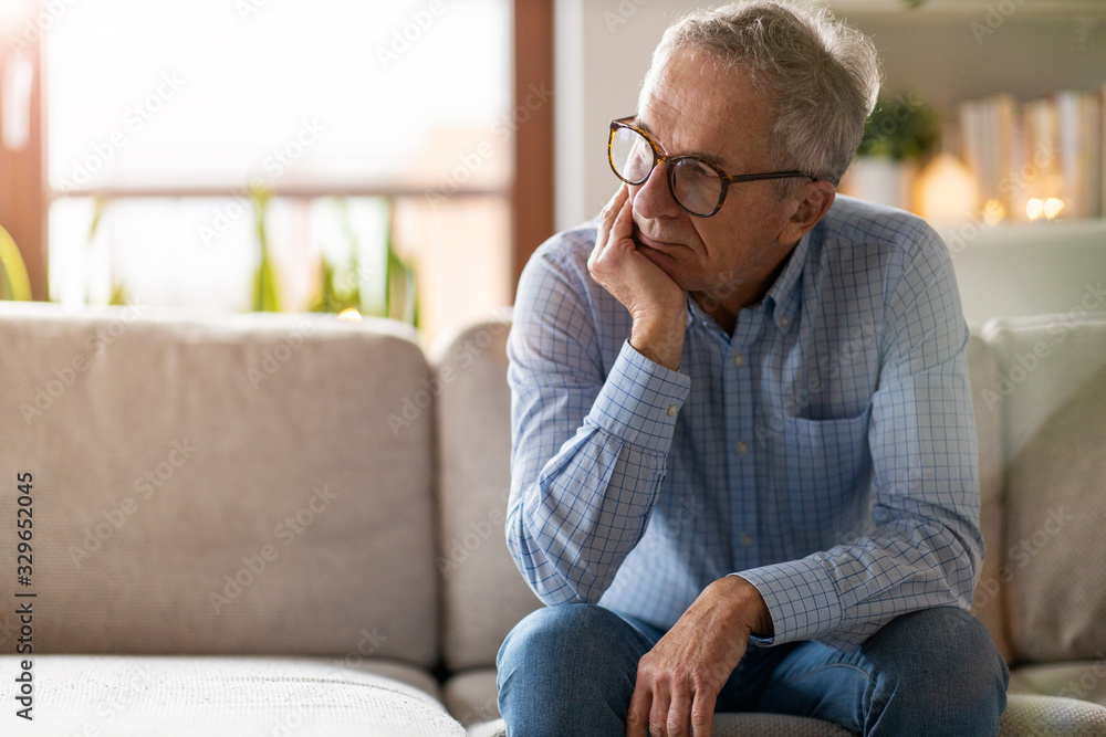 Fototapeta Worried senior man sitting alone in his home