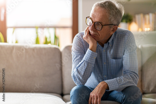 Fototapeta Worried senior man sitting alone in his home