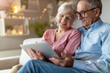 Leinwanddruck Bild - Mature couple using a laptop while relaxing at home