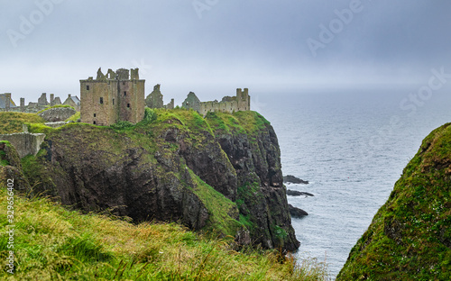 Dunnottar Castle ruins perched on the cliffs of Aberdeenshire coat, Scotland, on a foggy and rainy summer day Wallpaper Mural