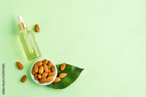 Fototapeta flat lay almond oil and whole nut for skincare, massage, cooking on green background. obraz