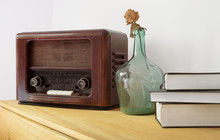 Vintage Radio Made Of Wood, Green Vase And Old Books On A Table