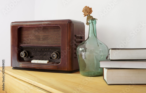 Vintage radio made of wood, green vase and old books on a table Wallpaper Mural