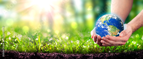 Fotografía Hands Holding Planet Earth In Lush Green Environment With Soil And Sunlight - Ea