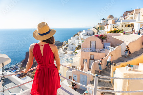 Travel vacation greece santorini island woman in red dress traveling in Europe looking at Oia village view, luxury holiday Canvas Print