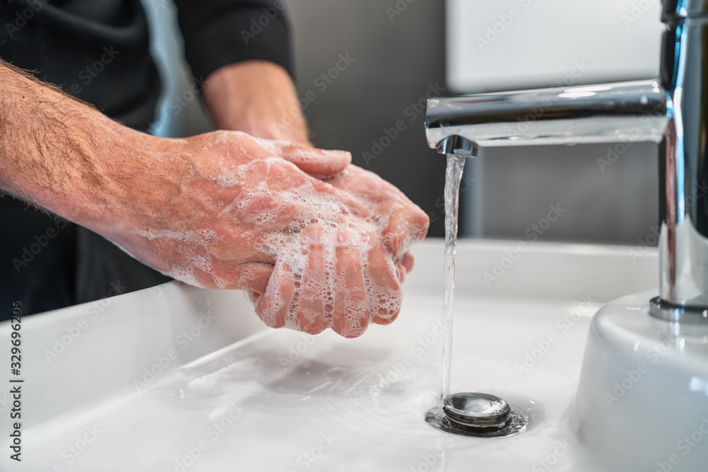 Fototapeta Corona virus travel prevention man showing hand hygiene washing hands with soap in hot water for coronavirus germs spreading protection.