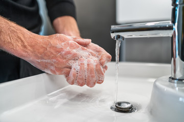 Corona virus travel prevention man showing hand hygiene washing hands with soap in hot water for coronavirus germs spreading protection.