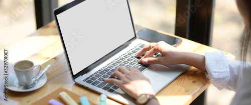 Close up view of young female university student typing on laptop in coffee shop Canvas Print