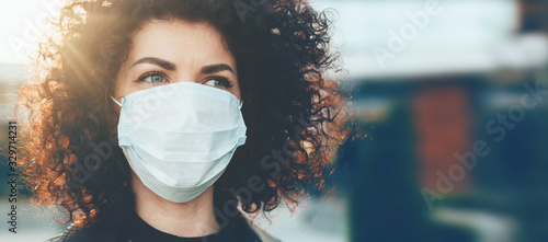Obraz Lovely curly haired caucasian lady protecting herself from viruses while wearing special mask - fototapety do salonu