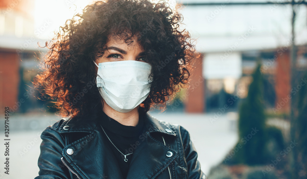 Fototapeta Curly haired caucasian lady posing outside while wearing a protective mask
