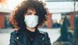 Leinwandbild Motiv Curly haired caucasian lady posing outside while wearing a protective mask