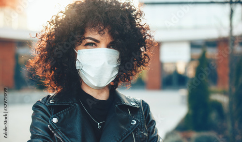 Obraz na plátně Curly haired caucasian lady posing outside while wearing a protective mask