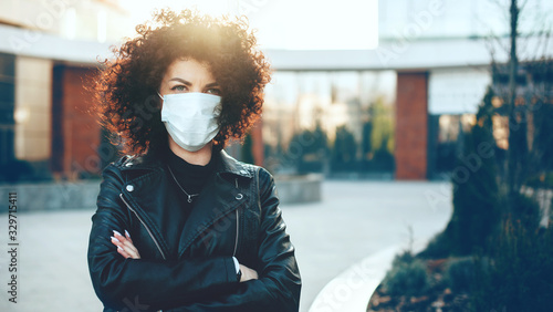 Caucasian woman posing with crossed hands while wearing an anti flu mask and loo Lerretsbilde