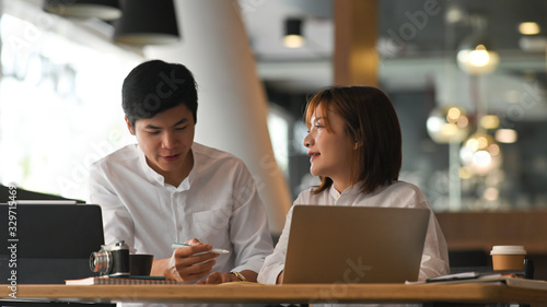 Photo of young woman and man in white shirt working as financial developer team working together while sitting at the modern wooden table with luxury office as background Canvas Print
