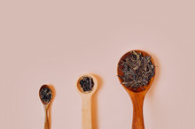 Three Wooden Vintage Spoons Of Different Sizes Filled With Dry Granules And Dried Tea Leaves On A Delicate Peach Pink Background.