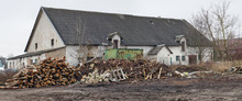 An Illegal Dump Of Garbage And Wood Waste Was Formed Near A Rustic Old Brick Shed