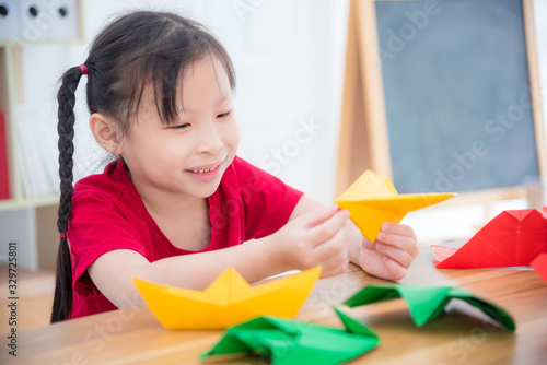 Photo Little asian girl doing paper airplane from paper folding at school