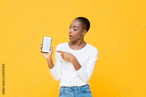 Photo Young African American woman looking and pointing at mobile phone isolated on ye