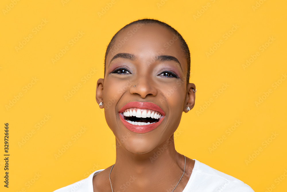 Fototapeta Close up portrait of friendly happy African American woman smiling on isolated colorful yellow background
