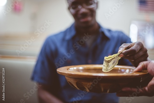 Fototapeta Closeup of a man donating money under the lights with a blurry background obraz