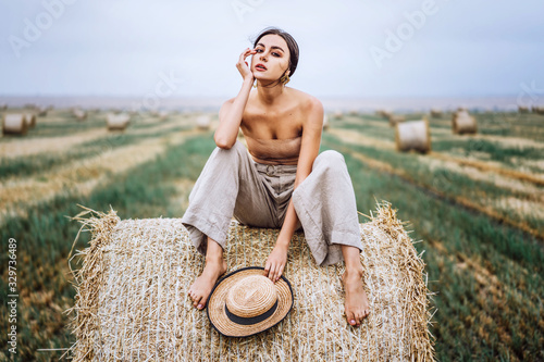 Valokuvatapetti Barefoot brunette in linen pants and bare shoulders sitting on a hay bales in warm autumn day