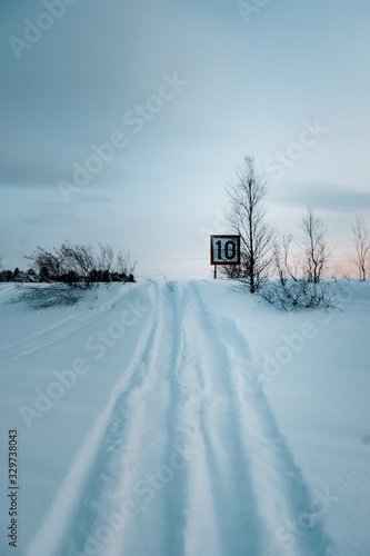 Fotografía Vertical shot of a speed limit sign on the road covered with snow