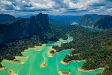 Aerial Drone View Looking Down Onto Tiny, Jungle Covered Islands In A Huge Lake Surrounded By Limestone Cliffs. (Cheow Lan Lake, Khao Sok)