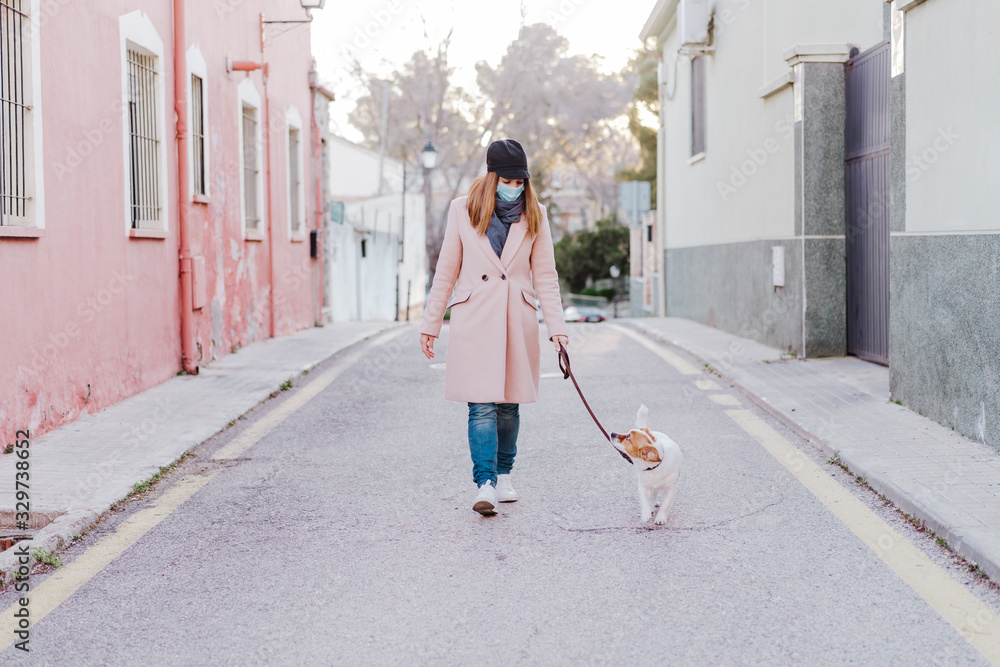 Fototapeta caucasian woman in the street wearing protective mask and walking with her dog. corona virus concept