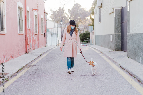 caucasian woman in the street wearing protective mask and walking with her dog Lerretsbilde