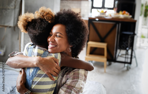 Portrait of a joyful mother and her daughter smiling and hugging Canvas Print