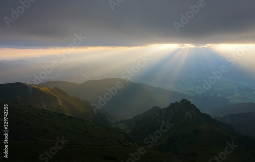 Stunning shot of a mountain range with sunlight on a cloudy sky Tablou Canvas