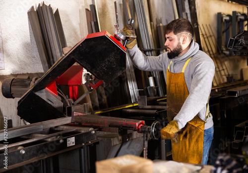 Fototapeta Worker cuts metal profile pipe on a band saw