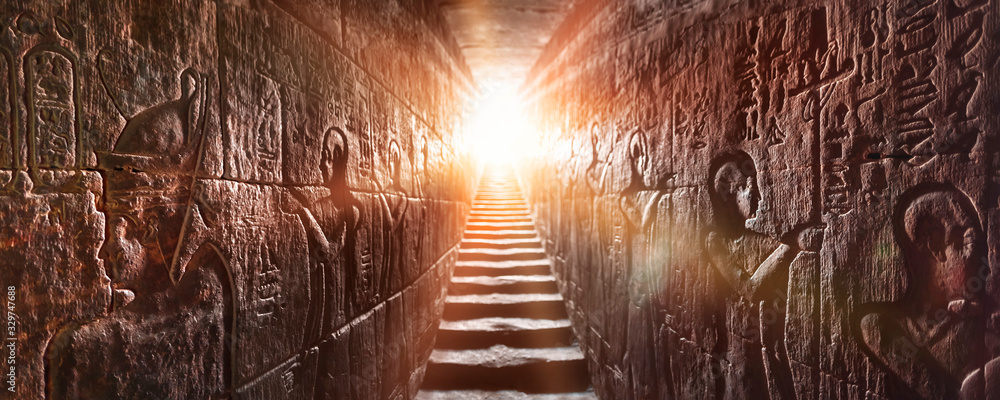 Fototapeta Egypt Edfu temple, Aswan. Passage flanked by two glowing walls full of Egyptian hieroglyphs, illuminated by a warm orange backlight from a door