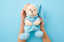 Girl Hands Holding Sleepy Teddy Bear In Blue Pajama And Hat. Pastel Table Background. Kids Best Friend For Sweet Dreams. Point Of View Shot. Closeup.