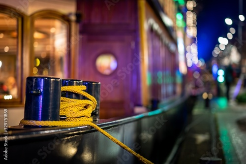 Closeup of a mooring bollard with a yellow rope tied around it and bokeh lights Wallpaper Mural