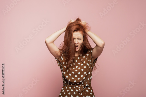 Tablou Canvas Crying emotional angry woman screaming on pink studio background
