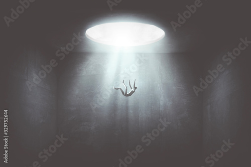 Foto man falling down from a hole of light, surreal concept