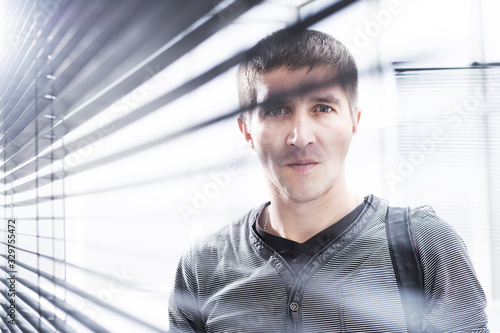 serious young man looking through window blind