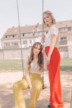 Portrait Of Two Young Women In Red And Yellow Trousers Sitting On The Swings At The Playground In Urban Environment
