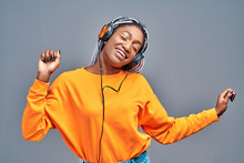 Afro Woman In Headphones Listening To Music And Dancing Over Grey Studio Background