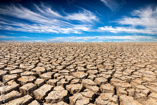 Photo Land with dry and cracked ground and fluffy white clouds scatter in full light clear sky