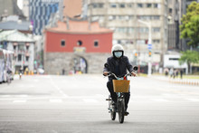 A Chinese Man, Wearing A Face Mask To Protect Himself From The Novel Coronavirus 2019-nCoV Or COVID-19 Is Riding A Scooter In Taipei, Taiwan.