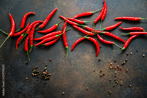 A lot of chili peppers on a kitchen table. Top view. Canvas Print