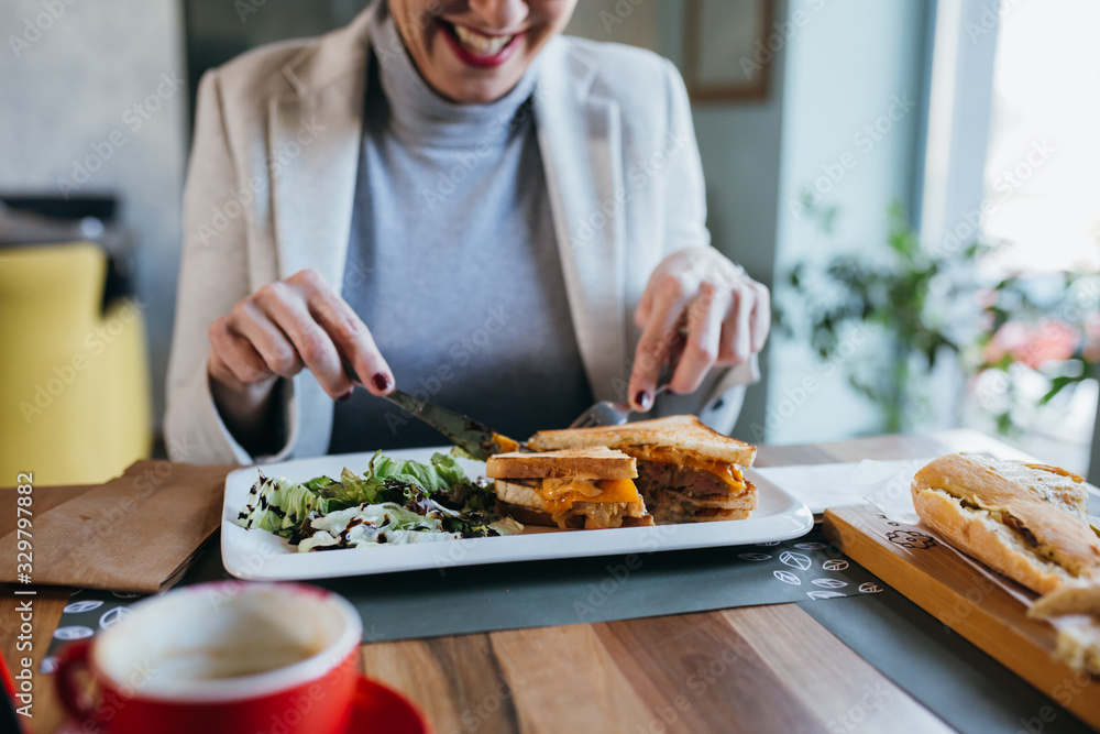 Fototapeta close up woman eating breakfast or lunch in restaurant