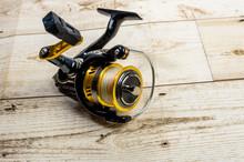 Golden Fishing Reel On Wooden ...