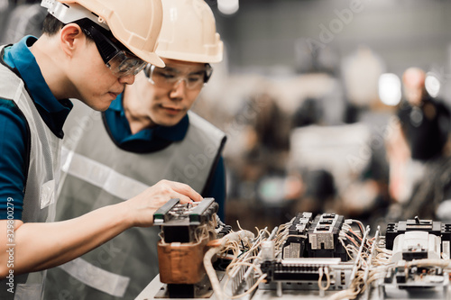 Fotografering Two asian maintenance engineers discuss inspect relay checking information and protection system on a tablet computer in a factory