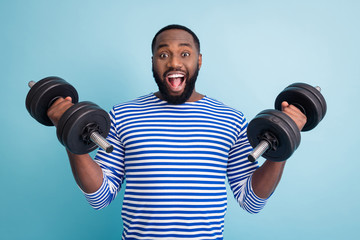 Photo of cool funny handsome dark skin guy open mouth lifting two heavy dumbbells weight practicing hard gym strong man wear striped sailor shirt isolated blue color background