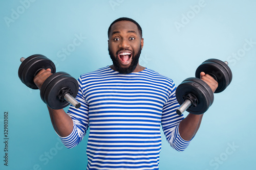 obraz PCV Photo of cool funny handsome dark skin guy open mouth lifting two heavy dumbbells weight practicing hard gym strong man wear striped sailor shirt isolated blue color background
